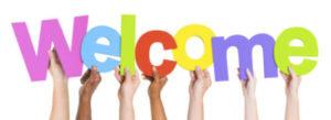The word Welcome held in multi-ethnic hands